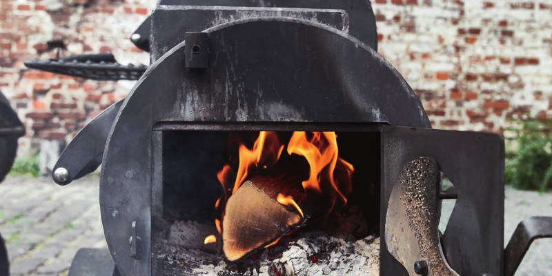 Feuer mit Holzscheiten in der Smooker Brennkammer