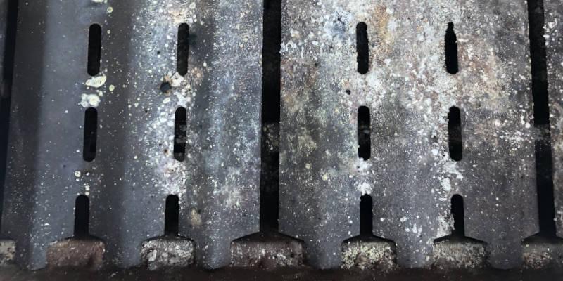 Verschmutzte Brennerabdeckungen eines Gasgrills