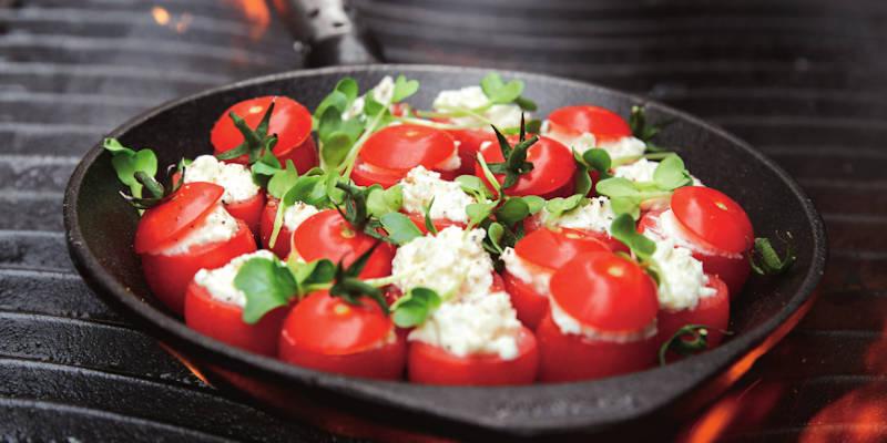 Grillpfanne mit gefüllten Tomaten auf dem Grill