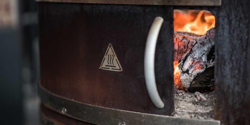 Brennkammer des Feuertopf Grills mit brennendem Holz